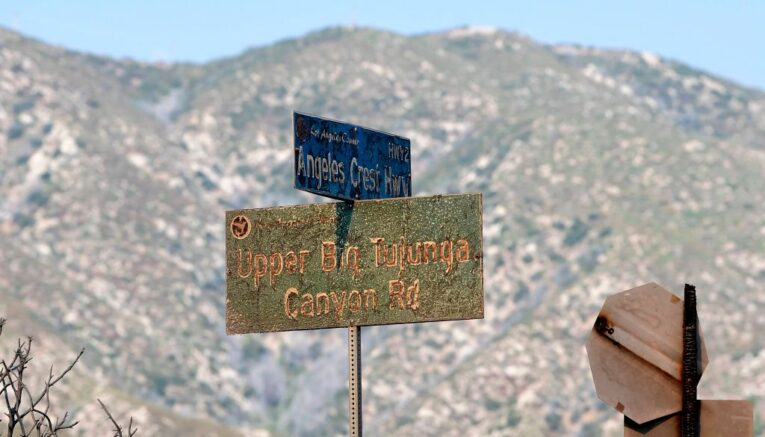 Fire-damaged road signs remain standing at the intersection of the Angeles Crest Highway and Upper Big Tujunga Canyon Road in the Angeles National Forest on September 23, 2020 in Los Angeles, California. - Containment has grown to 38 percent as one of the biggest fires in the history of Los Angeles County grows to over 113,000 acres. (Photo by Frederic J. BROWN / AFP) (Photo by FREDERIC J. BROWN/AFP via Getty Images)
