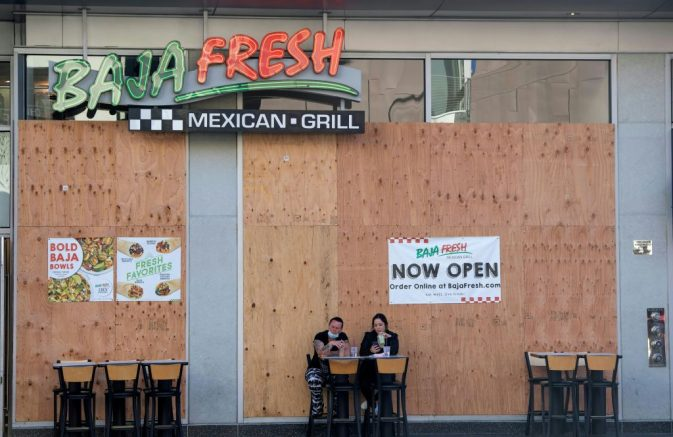 People wearing facemasks have lunch outside of a boarded Baja Fresh restaurant on Hollywood Boulevard amid the Coronavirus pandemic, November 10, 2020, in Hollywood, California. - The United States recorded its 10 millionth case of the coronavirus Monday, according to a count by Johns Hopkins University, the same day that Pfizer and BioNTech announced their vaccine showed 90 percent effectiveness.<br /> Shortly before 1400 GMT on November 9, 2020 the tracker by the Baltimore-based university showed 10,018,278 cases recorded in the US since the pandemic began, and 237,742 deaths. Both are the highest tolls in absolute terms in the world. (Photo by VALERIE MACON / AFP) (Photo by VALERIE MACON/AFP via Getty Images)