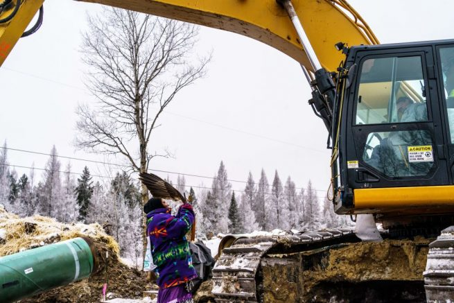 A Native American environmental activist shows an eagle feather to a construction worker in a bulldozer at the construction site for the Line 3 oil pipeline near Palisade, Minnesota on January 9, 2021. - Line 3 is an oil sands pipeline which runs from Hardisty, Alberta, Canada to Superior, Wisconsin in the United States. In 2014, a new route for the Line 3 pipeline was proposed to allow an increased volume of oil to be transported daily. While that project has been approved in Canada, Wisconsin, and North Dakota, it has sparked continued resistance from climate justice groups and Native American communities in Minnesota. While many people are concerned about potential oil spills along Line 3, some Native American communities in Minnesota have opposed the project on the basis of treaty rights. (Photo by Kerem Yucel / AFP) (Photo by KEREM YUCEL/AFP via Getty Images)