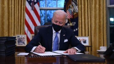TOPSHOT - US President Joe Biden sits in the Oval Office as he signs a series of orders at the White House in Washington, DC, after being sworn in at the US Capitol on January 20, 2021. - US President Joe Biden signed a raft of executive orders to launch his administration, including a decision to rejoin the Paris climate accord. The orders were aimed at reversing decisions by his predecessor, reversing the process of leaving the World Health Organization, ending the ban on entries from mostly Muslim-majority countries, bolstering environmental protections and strengthening the fight against Covid-19. (Photo by Jim WATSON / AFP) (Photo by JIM WATSON/AFP via Getty Images)