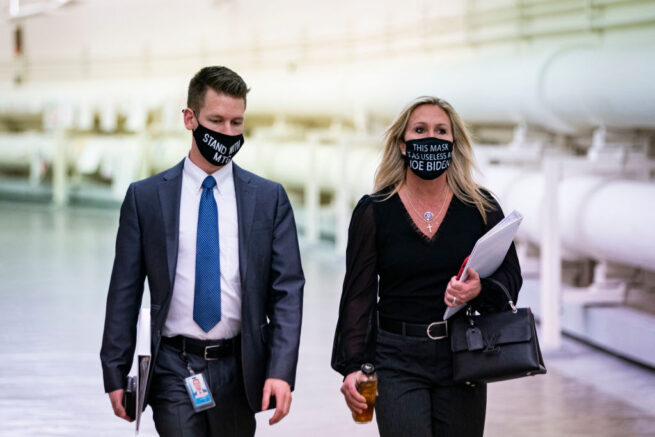 "WASHINGTON, DC - FEBRUARY 25: Rep. Marjorie Taylor Greene (R-GA) wears a protective mask bearing the words ""This mask is as useless as Joe Biden,"" as she walks with an aide to a vote in the Cannon Tunnell on Capitol Hill, on February 25, 2021 in Washington, DC. (Photo by Al Drago/Getty Images)"