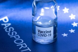 """A picture taken on March 3, 2021 in Paris shows a vaccine vial reading """"Covid-19 vaccine"""" on an European passport. (Photo by JOEL SAGET / AFP) (Photo by JOEL SAGET/AFP via Getty Images)"""
