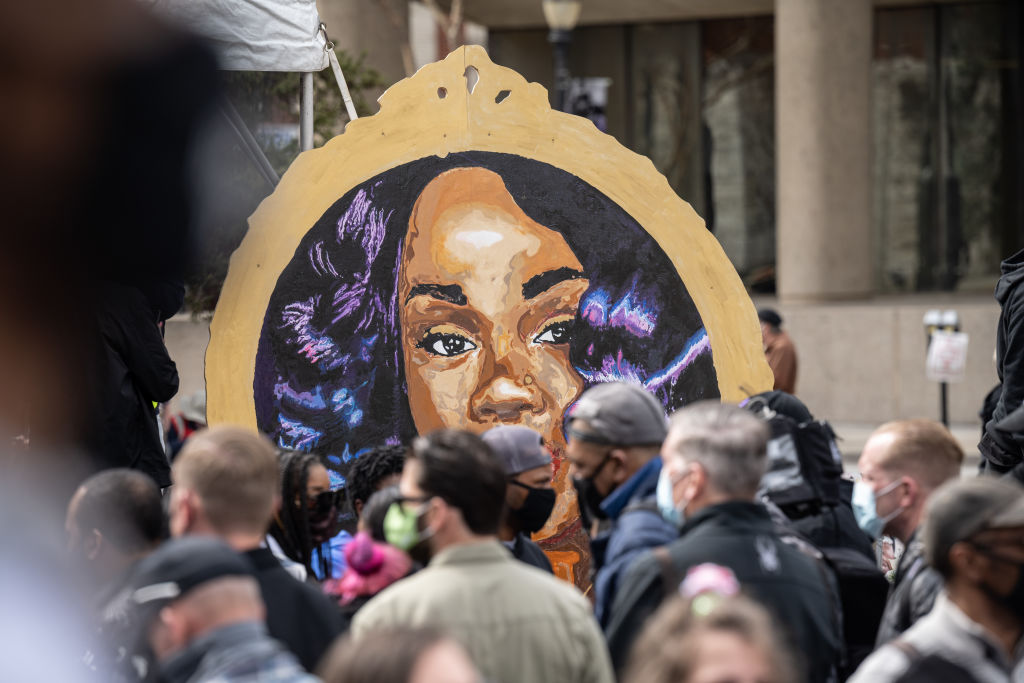 LOUISVILLE, KY - MARCH 13: A portrait of Breonna Taylor is seen before the crowd during a memorial protest for her in Jefferson Square Park on March 13, 2021 in Louisville, Kentucky. Today marks the one year anniversary since Taylor was killed in her apartment during a botched no-knock raid executed by LMPD. (Photo by Jon Cherry/Getty Images)