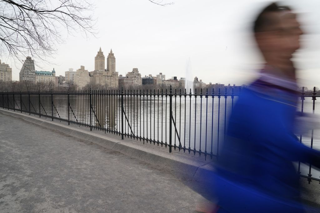 With the iconic Eldorado Apartments in the background a man jogs around the Jacqueline Kennedy Onassis Reservoir in Central Park March 16, 2021 in New York. (Photo by TIMOTHY A. CLARY / AFP) (Photo by TIMOTHY A. CLARY/AFP via Getty Images)
