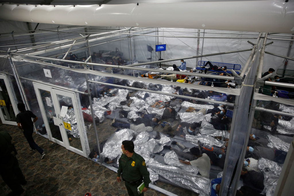 Young minors lie inside a pod at the Donna Department of Homeland Security holding facility, the main detention center for unaccompanied children in the Rio Grande Valley run by the US Customs and Border Protection, (CBP), in Donna, Texas on March 30, 2021. - The minors are housed by the hundreds in eight pods that are about 3,200 square feet in size. Many of the pods had more than 500 children in them. The Biden administration on Tuesday for the first time allowed journalists inside its main detention facility at the border for migrant children, revealing a severely overcrowded tent structure where more than 4,000 kids and families were crammed into pods and the youngest kept in a large play pen with mats on the floor for sleeping. (Photo by Dario Lopez-Mills / POOL / AFP) (Photo by DARIO LOPEZ-MILLS/POOL/AFP via Getty Images)