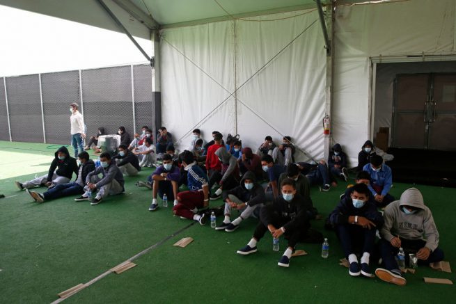 Young minors who tested positive for Covid-19 sit in the ground at the Donna Department of Homeland Security holding facility, the main detention center for unaccompanied children in the Rio Grande Valley run by the US Customs and Border Protection, (CBP), in Donna, Texas on March 30, 2021. - The Biden administration on Tuesday for the first time allowed journalists inside its main detention facility at the border for migrant children, revealing a severely overcrowded tent structure where more than 4,000 kids and families were crammed into pods and the youngest kept in a large play pen with mats on the floor for sleeping. (Photo by Dario Lopez-Mills / POOL / AFP) (Photo by DARIO LOPEZ-MILLS/POOL/AFP via Getty Images)