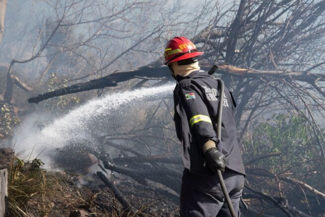 A fire-fighter dampens smouldering vegetation, finally getting a fierce forest fire under control on the foothills of Table Mountain in Cape Town on April 19, 2021. - The fire, which broke out on April 18, 2021 in the foothills of the city's landmark Table Mountain before spreading to the University of Cape Town (UCT), forced hundreds of students to flee. (Photo by RODGER BOSCH / AFP) (Photo by RODGER BOSCH/AFP via Getty Images)