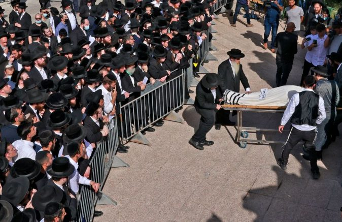 Ultra-Orthodox Jewish men take part in a funeral ceremony in Jerusalem for a victim of an overnight stampede during a religious gathering in northern Israel, on April 30, 2021. - A massive stampede at a densely packed Jewish pilgrimage site killed at least 44 people in Israel, blackening the country's largest COVID-era gathering. (Photo by Menahem KAHANA / AFP) (Photo by MENAHEM KAHANA/AFP via Getty Images)