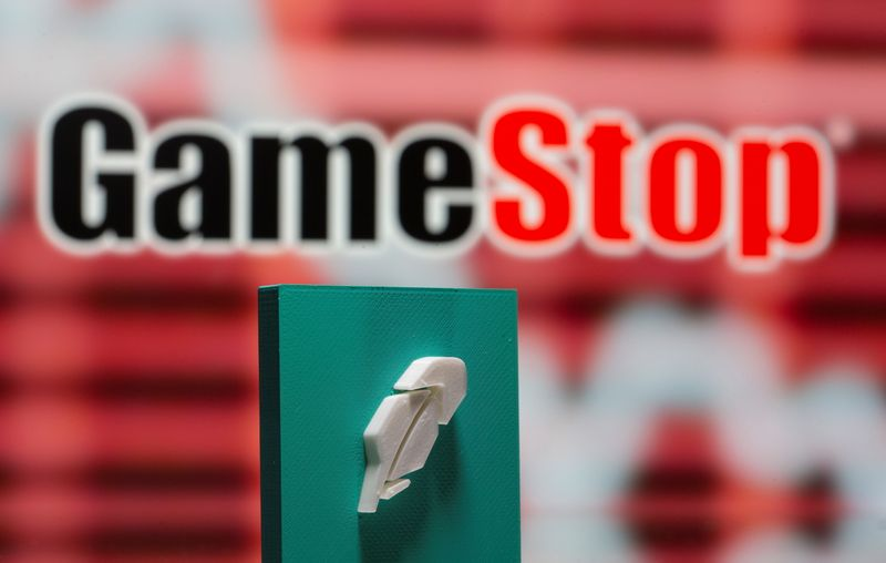 A 3d printed Robinhood logo is seen in front of displayed GameStop logo in this illustration