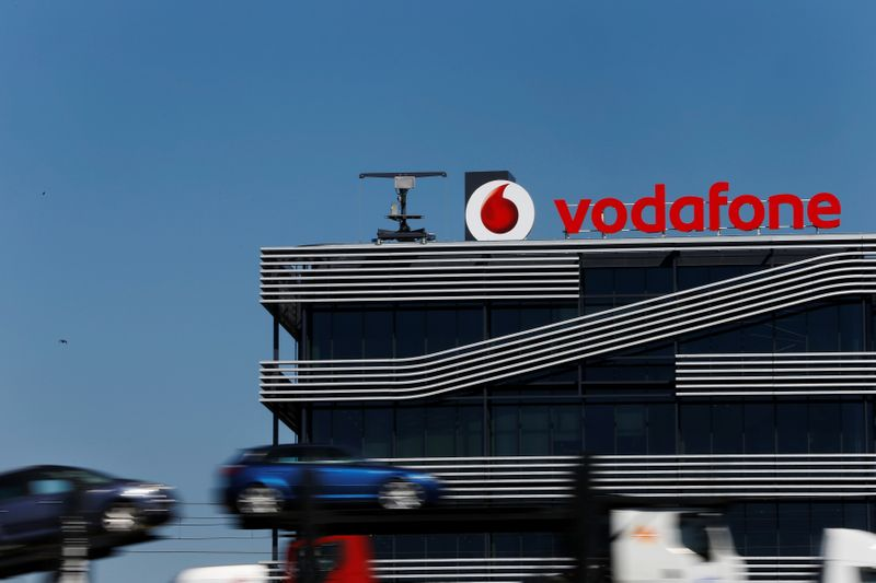 FILE PHOTO: A truck carrying cars speeds past the headquarters of Vodafone in Madrid