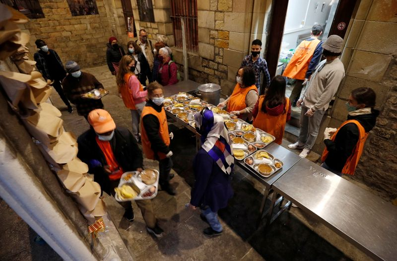 People carry food trays during a charity Ramadan dinner in the cloister at Santa Anna church in Barcelona