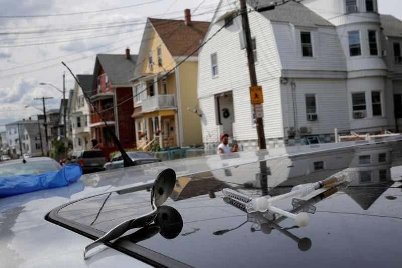 FILE PHOTO: A full syringe, empty syringe and spoon sit on the roof of the car in Lynn