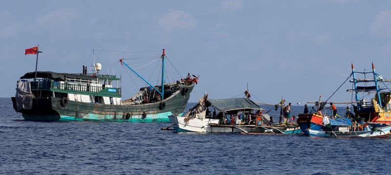 FILE PHOTO: A Chinese fishing vessel is anchored next to Filipino fishing boats at the disputed Scarborough Shoal