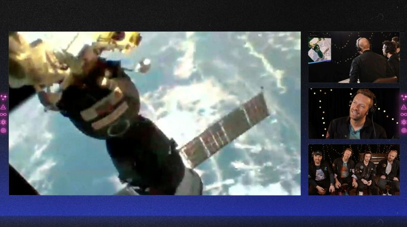 Members of Coldplay watch the view from the window of International Space Station during an interview with French ESA astronaut Thomas Pesquet