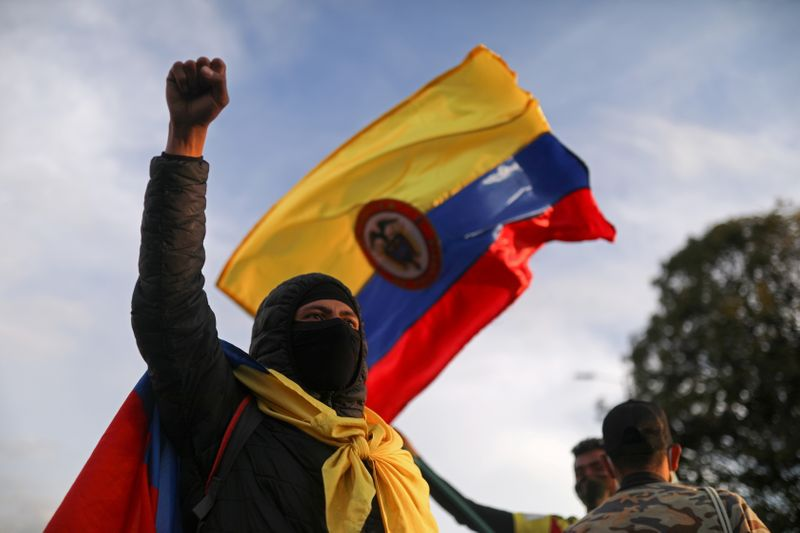 FILE PHOTO: A demonstrator takes part in a protest demanding government action to tackle poverty, police violence and inequalities in the health and education systems, in Bogota,