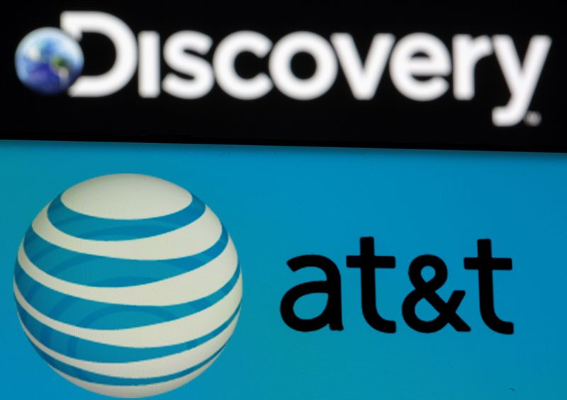 AT&T logo is seen on a smartphone in front of displayed Discovery logo in this illustration