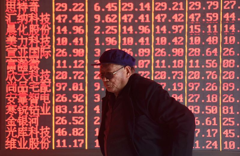 Man stands in front of an electronic board displaying stock information at a brokerage firm in Hangzhou