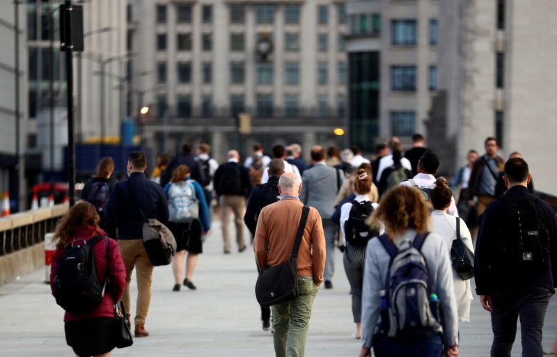 FILE PHOTO: Commuters walk across the London Bridge during the morning rush hour in London