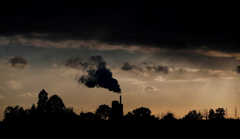 FILE PHOTO: Smoke rises above a factory at sunset in Rugby