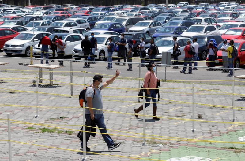 FILE PHOTO: Volkswagen employees arrive to the plant to attend a training before the reopening of the automotive sector as the spread of the coronavirus disease (COVID-19) continues, in Puebla
