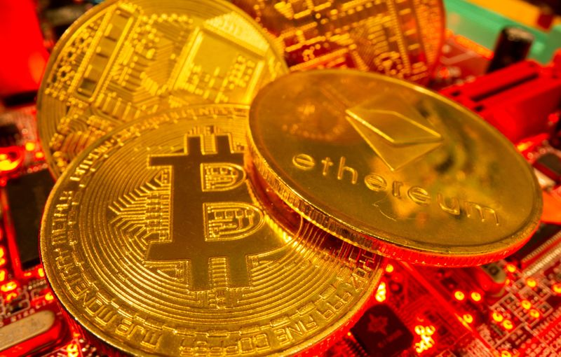 FILE PHOTO: Representations of the virtual currency Bitcoin and Ethereum stand on a motherboard in this picture illustration