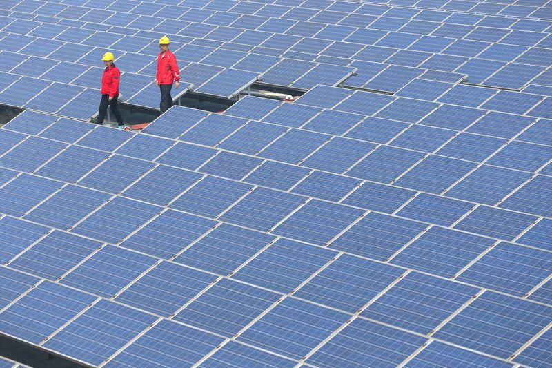 Workers walk past solar panels in Jimo