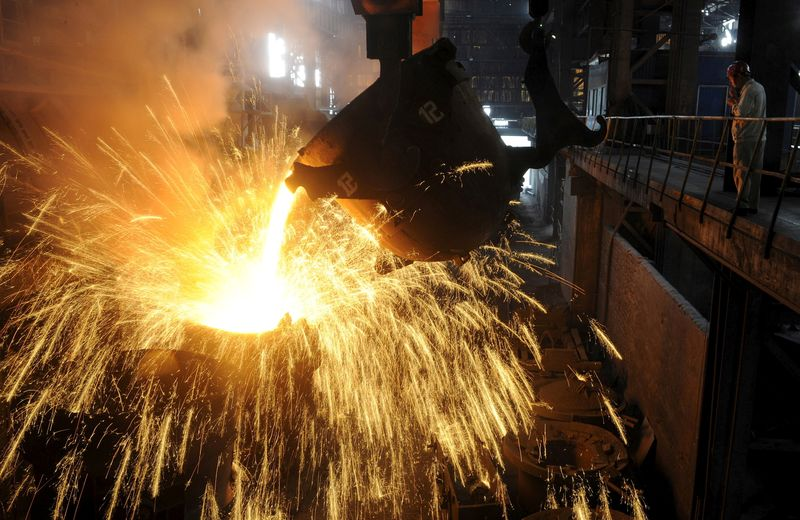 FILE PHOTO: An employee monitors molten iron being poured into a container at a steel plant in Hefei