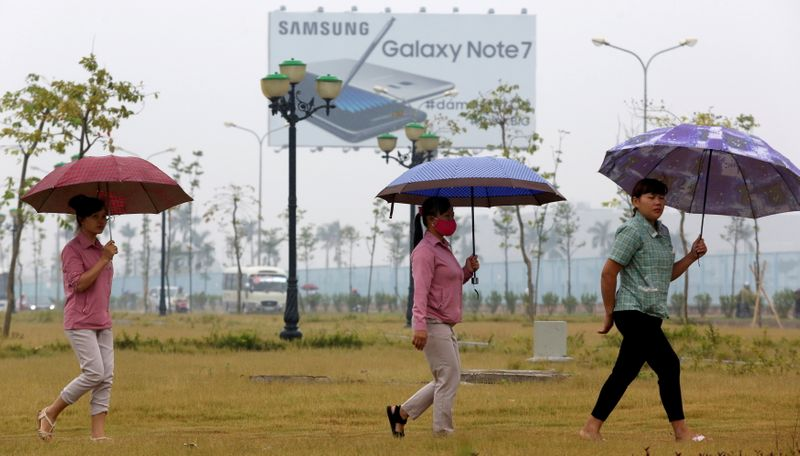 FILE PHOTO: Employees pass a billboard advertisement for the Samsung Galaxy Note 7 on the way to work at the Samsung factory in Thai Nguyen province, north of Hanoi