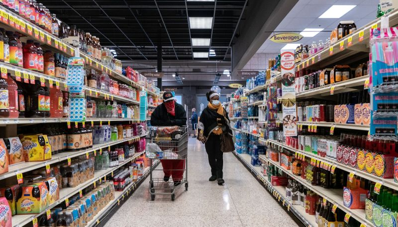 Shoppers browse in a supermarket while wearing masks in St Louis