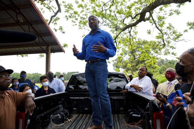 U.S. Sen. Rev. Raphael Warnock speaks with Black farmers in Byromville, Ga., on Tuesday, May 4, 2021. Warnock addressed targeted federal relief in the American Rescue Plan for farmers of color and vowed to tackle the history of discriminatory practices by the United States Department of Agriculture. (Riley Bunch/The Daily Times via AP)