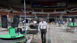 Ken Bennett, the former Republican Arizona Secretary of State, walks the floor of the Arizona Veterans Memorial Coliseum during setup of a 2020 election audit called for by the Arizona Republican lead Senate Thursday, April 22, 2021, in Phoenix. An Arizona judge on Friday temporarily halted an audit of the 2020 election results from Maricopa County as long as Democrats put up $1 million to fund any potential increase in costs. (AP Photo/Ross D. Franklin)