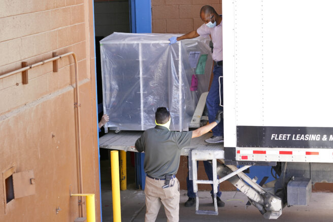 FILE - In this Wednesday, April 21, 2021 file photo, officials unload election equipment into the Veterans Memorial Coliseum at the state fairgrounds in Phoenix. Maricopa County officials began delivering equipment used in the November election won by President Joe Biden on Wednesday and will move 2.1 million ballots to the site Thursday so Republicans in the state Senate who have expressed uncertainty that Biden's victory was legitimate can recount them and audit the results. (AP Photo/Matt York)