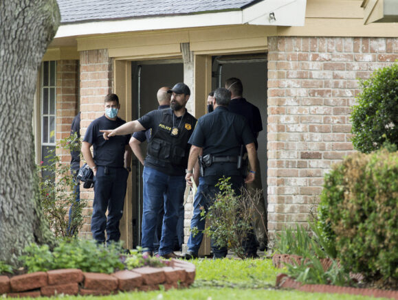 Law enforcement officials investigate the site of a human smuggling case, where more than 90 undocumented immigrants were found inside a home on the 12200 block of Chessington Drive on Friday, April 30, 2021, in Houston. A Houston Police officials said the case will be handled by federal authorities. ( Godofredo A. Vásquez/Houston Chronicle via AP)