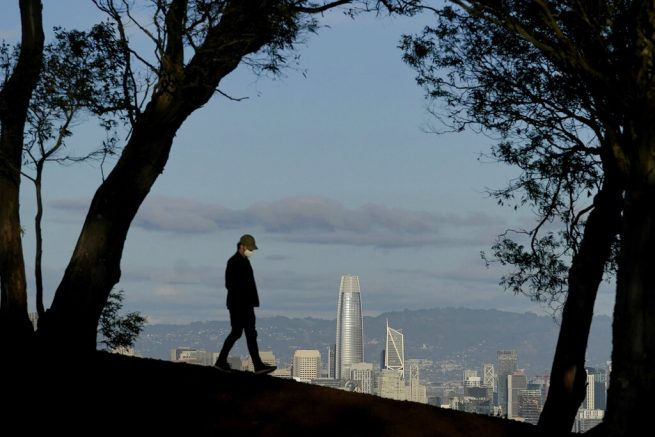 FILE - In this Dec. 17, 2020, file photo, a person wearing a face mask walks atop Tank Hill in front of the skyline during the coronavirus pandemic in San Francisco. Los Angeles and San Francisco are poised Tuesday, May 4, to be the only major urban areas in the state to meet guidelines to move into the least-restrictive tier, amid the pandemic. (AP Photo/Jeff Chiu, File)