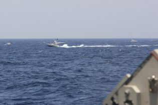 """In this image provided by the U.S. Navy, an Iranian Islamic Revolutionary Guard Corps Navy (IRGCN) fast in-shore attack craft (FIAC), a type of speedboat armed with machine guns, speeds near U.S. naval vessels transiting the Strait of Hormuz, Monday, May 10, 2021. U.S. officials say a group of 13 armed speedboats of Iran's Revolutionary Guard made """"unsafe and unprofessional"""" high-speed maneuvers toward U.S. Navy vessels in the Strait of Hormuz on Monday. A U.S. Coast Guard cutter fired warning shots when two of the Iranian boats came dangerously close. (U.S. Navy via AP)"""