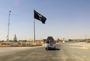 """FILE - In this Tuesday, July 22, 2014, file photo, a motorist passes by a flag of the Islamic State group in central Rawah, 175 miles (281 kilometers) northwest of Baghdad, Iraq, nearly six weeks since a Sunni militant blitz led by the Islamic State extremist group seized large swaths of northern and western Iraq. The head of a United Nations team investigating atrocities in Iraq says it has found """"clear and compelling evidence"""" that Islamic State extremists committed genocide against the Yazidi minority in 2014. (AP Photo/File)"""