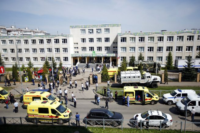 Ambulances and police cars and a truck are parked at a school after a shooting in Kazan, Russia, Tuesday, May 11, 2021. Russian media report that several people have been killed and wounded in a school shooting in the city of Kazan. Russia's state RIA Novosti news agency reported the shooting took place Tuesday morning, citing emergency services. (AP Photo/Roman Kruchinin)