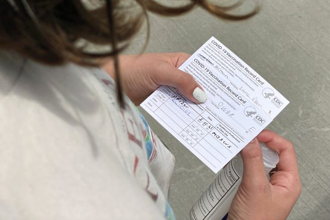 Jane Ellen Norman, 12, holds vaccination cards for her and her 14-year-old brother Owen outside Mercedes-Benz Stadium in Atlanta on Tuesday, May 11, 2021. The two were vaccinated Tuesday morning, after U.S. regulators expanded use of Pfizer's COVID-19 shot to those as young as 12. (AP Photo/Angie Wang)