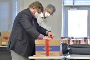 From left, election auditors Harri Hursti and Mark Lindeman, seal maintenance logs and voting machine keys in a box Tuesday, May 11, 2021, in Pembroke, N.H., at the site of a forensic audit of a New Hampshire legislative election. The audit, which will be live streamed from the Edward Cross Training Center, in Pembroke, is to review the November 2020 Windham, N.H., election for four state legislative seats. (AP Photo/Josh Reynolds)