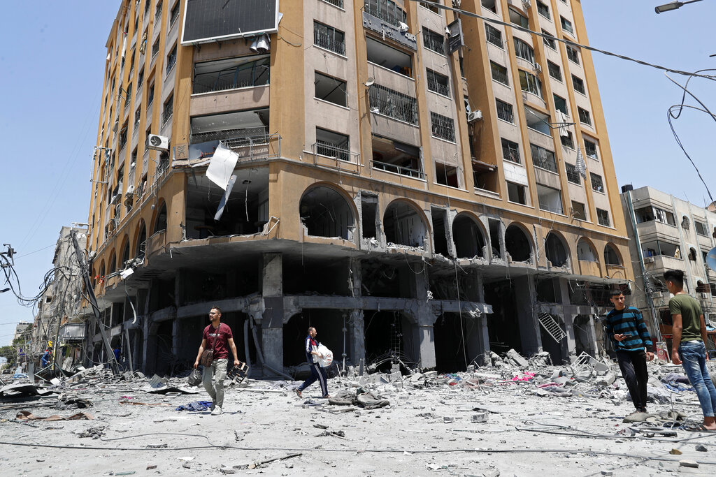 People inspect the rubble of a damaged building which was hit by an Israeli airstrike, in Gaza City, Wednesday, May 12, 2021. (AP Photo/Adel Hana)