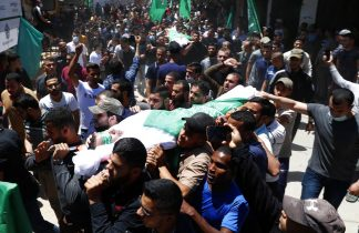 Mourners carry the body of Bassem Issa, front, top Hamas' commander in Gaza City and other bodies, during a funeral of thirteen Hamas militants outside the mosque in Gaza City, Thursday, May 13, 2021. (AP Photo/Adel Hana)