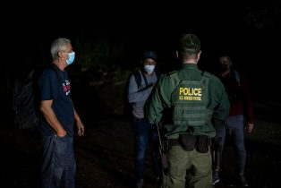 An agent with Border Patrol speaks to a group of migrant men after being apprehended near the border between Mexico and the United States in Del Rio, Texas on May 16, 2021. - Crossings in Del Rio have risen significantly this year with many crossings earlier this year by Haitian migrants and now many coming to seek asylum from Venezuela. (Photo by Sergio FLORES / AFP) (Photo by SERGIO FLORES/AFP via Getty Images)