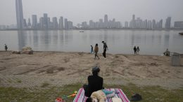 "A child wearing a mask rests along the Yangtze River on April 5, 2020, in Wuhan in central China's Hubei province just days before the lifting of the city's 76-day coronavirus lockdown. Associated Press photographer Ng Han Guan says of the photo: ""Personally the photo summed up my feelings being in the city which was unceremoniously shut down and residents forced into a comatose state of inactivity that somehow became normalized."" Though the riverbank scene is Idyllic, he says, ""in the background a slumbering city skyline is ready to hum back to life."" (AP Photo/Ng Han Guan)"