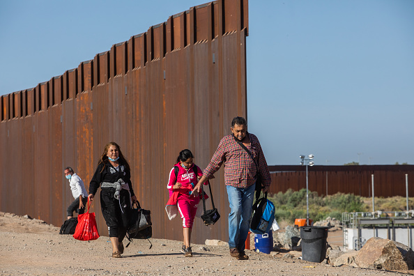 YUMA, AZ - MAY 13: A family of asylum seekers from Colombia walk through an opening in the wall at the US Mexico border to turn themselves in to US Border Patrol agents on May 13, 2021 in Yuma, Arizona. The Biden administration is trying to develop a plan to safely handle the surge of immigrants coming across the Southern border. (Photo by Apu Gomes/Getty Images)