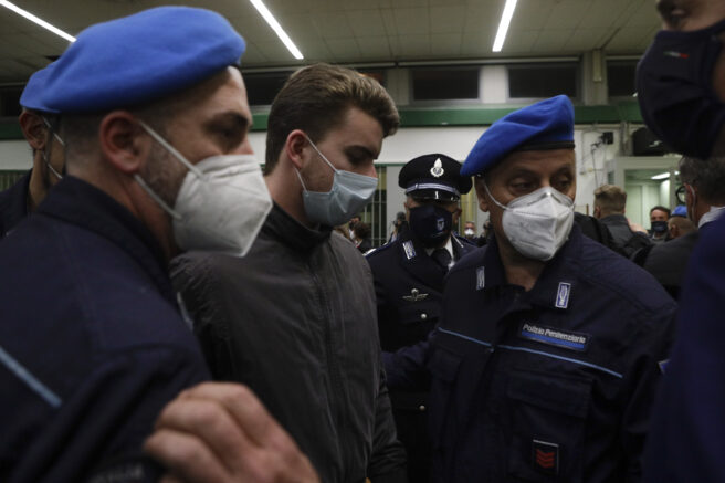 Gabriel Natale-Hjorth is escorted by police officers during the trial for the slaying of an Italian plainclothes police officer in summer 2019, in Rome, Wednesday, May 5, 2021. A jury in Rome has convicted two American friends in the 2019 slaying of a police officer in a drug sting gone awry, sentencing them to life in prison. The jury delivered more than 12 hours before delivering the verdicts late Tuesday against 21-year-old Finnegan Lee Elder and 20-year-old Gabriel Natale. (AP Photo/Gregorio Borgia)