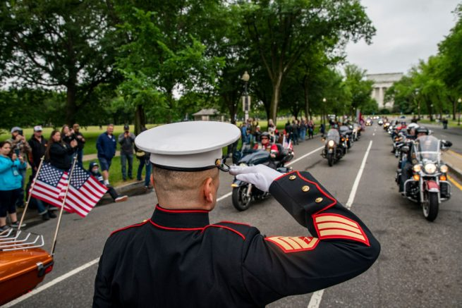 """WASHINGTON, DC - MAY 30: Staff Sgt. Tim Chambers salutes as motorcyclists participate in the """"Rolling to Remember"""" motorcycle rally as they ride past the Lincoln Memorial on May 30, 2021 in Washington, DC. The ride was to raise awareness of the critical issues facing the nation's veterans. (Photo by Tasos Katopodis/Getty Images)"""