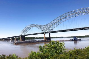 A tug boat pushes barges down the Mississippi River and under the Interstate 40 linking Tennessee and Arkansas on Friday, May 14, 2021, in Memphis, Tenn. The U.S. Coast Guard reopened a section of the river near Memphis on Friday, three days after river traffic was shut down when a crack was found in the bridge. (AP Photo/Adrian Sainz)