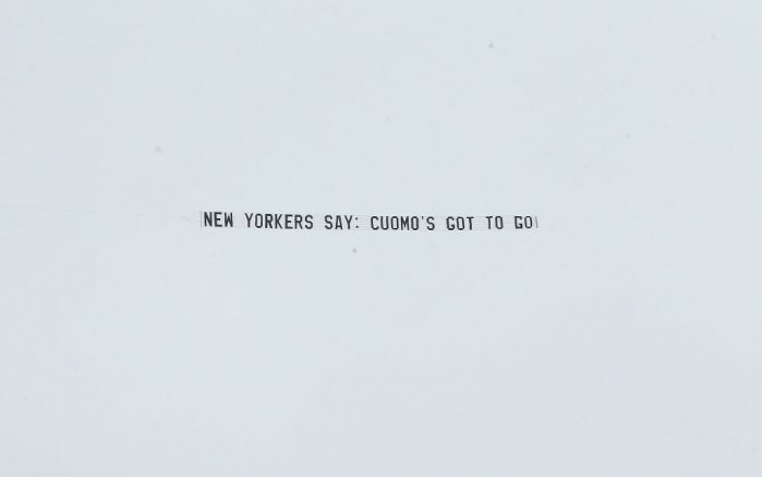 """ALBANY, NEW YORK - MARCH 17: A plane pulls a banner reading """"New Yorkers Say: Cuomo's Got To Go!"""" over the New York State Capitol in response to the sexual harassment allegations made by numerous women against Governor Andrew Cuomo on March 17, 2021 in Albany, New York. (Photo by Bennett Raglin/Getty Images for UltraViolet, Women's March, Girls for Gender Equity)"""