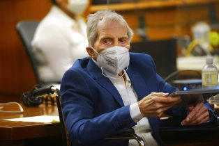 Robert Durst holds a device to read the real time spoken script as he appears in the courtroom of Judge Mark E. Windham as attorney's begin opening statements in the trial of the real estate scion charged with murder of longtime friend Susan Berman, at Los Angeles County Superior Court, Tuesday, May 18, 2021, in Inglewood, Calif. Durst's murder trial was delayed more than a year due to the Covid-19 pandemic. (Al Seib/Los Angeles Times via AP, Pool)