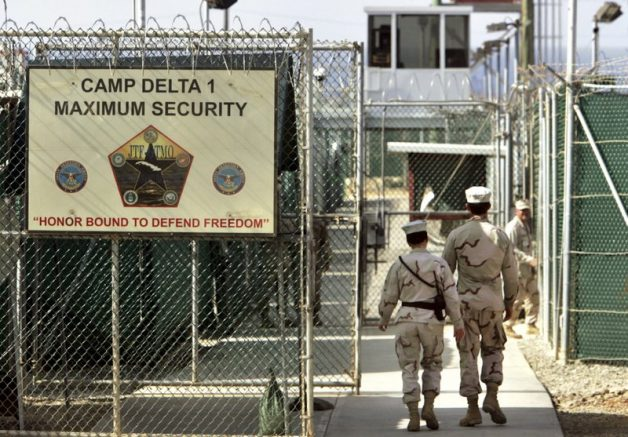 In this file photo reviewed by a U.S. Department of Defense official, U.S. military guards walk within Camp Delta military-run prison, at the Guantanamo Bay U.S. Naval Base, Cuba. (AP Photo/Brennan Linsley, File)